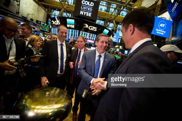 Timothy Whall chief executive officer of ADT Inc center right shakes hands with Tom Farley president of the NYSE Group Inc left during the company's...