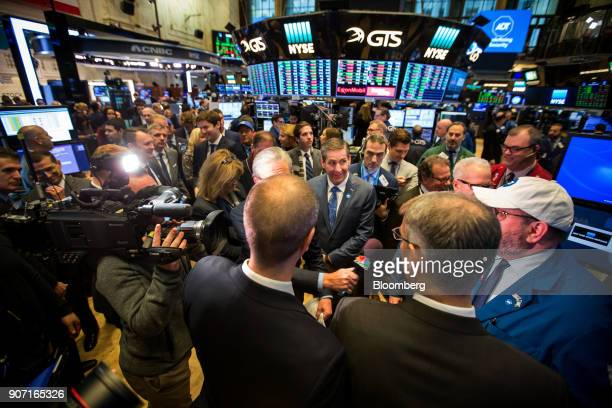 Timothy Whall chief executive officer of ADT Inc center watches a trader give a television interview during the company's initial public offering on...