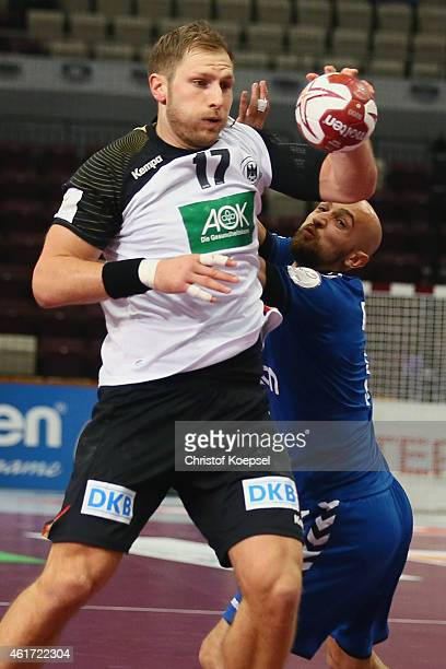 Timur Dibirov of Russia defends against Steffen Weinhold of Germany during the IHF Men's Handball World Championship group D match between Germany...