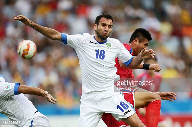 Timur Kapadze of Uzbekistan is challenged by Pak Kwang Ryong of DPR Korea during the 2015 Asian Cup match between Uzbekistan and DPR Korea at ANZ...