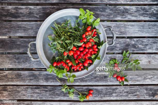 Tin bowl of rosehips on wood