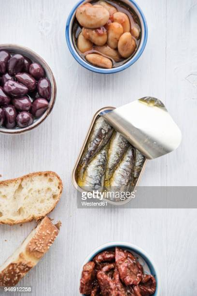 tin can of sardines in oil, bowls of pickled vegetables and slices of bread - sardine foto e immagini stock