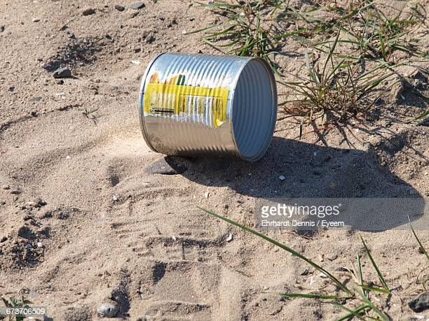 Tin Can On Sand At Beach During Sunny Day