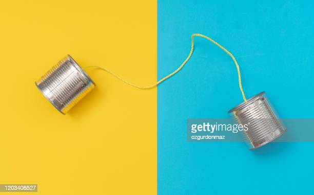 tin can phone on yellow and blue paper backgrounds - string stock pictures, royalty-free photos & images