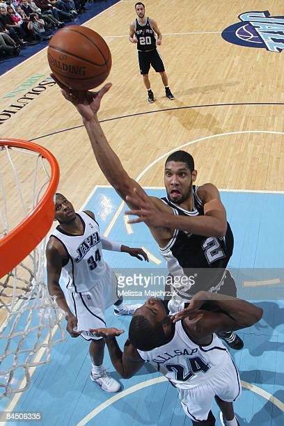 Tin Duncan of the San Antonio Spurs puts the shot up over Paul Millsap and CJ Miles of the Utah Jazz at EnergySolutions Arena on January 27 2009 in...