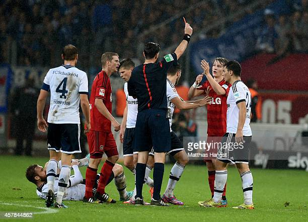 Tin Jedvaj of Bayer Leverkusen is shown the red card by the referee during the Bundesliga match between Bayer 04 Leverkusen and FC Schalke 04 at...