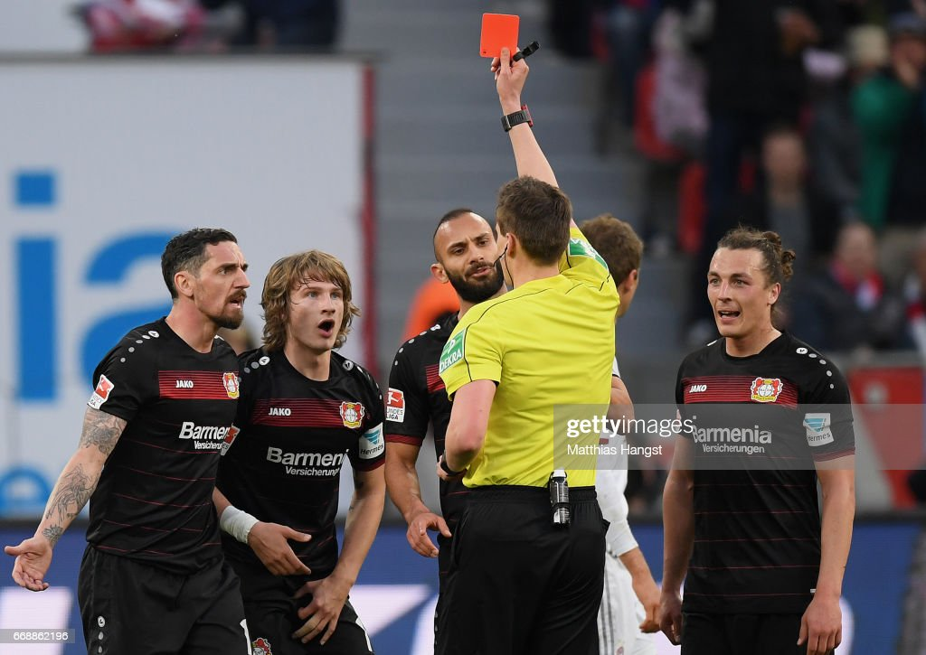 Tin Jedvaj (2R) of Leverkusen is shown a yellow-red card by referee Daniel Siebert during the Bundesliga match between Bayer 04 Leverkusen and Bayern Muenchen at BayArena on April 15, 2017 in Leverkusen, Germany.