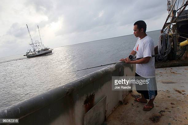 Tin Nguyen fishes as he passes time away in the shrimp boat he works on after the owner shut down operations due to the massive oil spill in the Gulf...