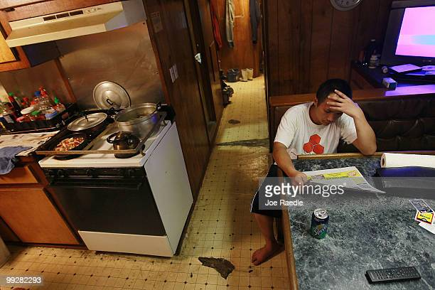 Tin Nguyen passes time away in the shrimp boat he works on after the owner shut down operations due to the massive oil spill in the Gulf of Mexico on...