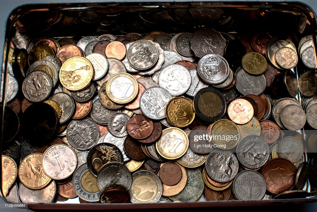 Tin of coins of various currencies : Stock Photo