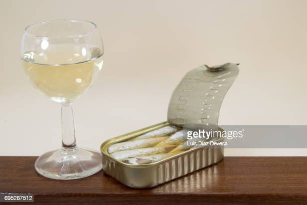 Tin of Sardines next to a glass of whte wine