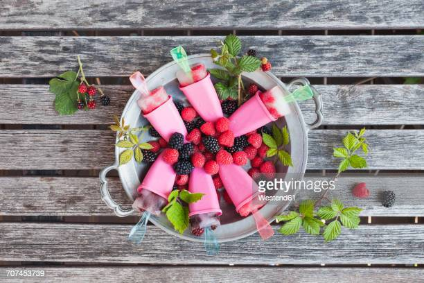 Tin plate of homemade lemonade ice lollies with raspberries and blackberries