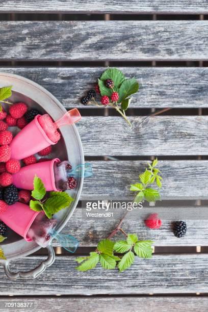 Tin plate of homemade lemonade ice lollies with raspberries and blackberries