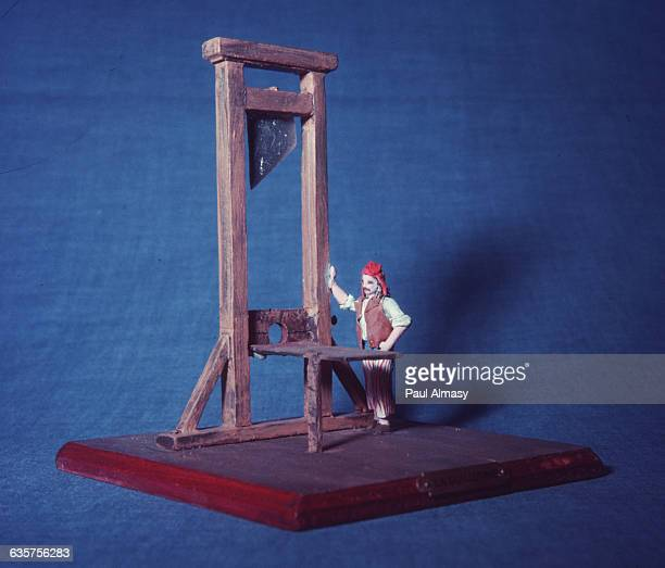 A tin soldier standing beside a model guillotine
