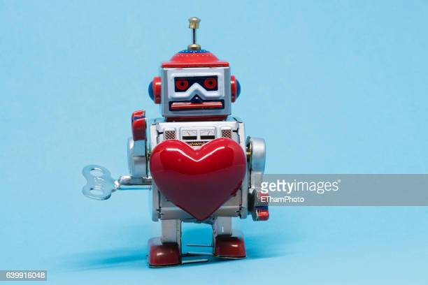 tin toy robot in love - wind up toy stock photos and pictures