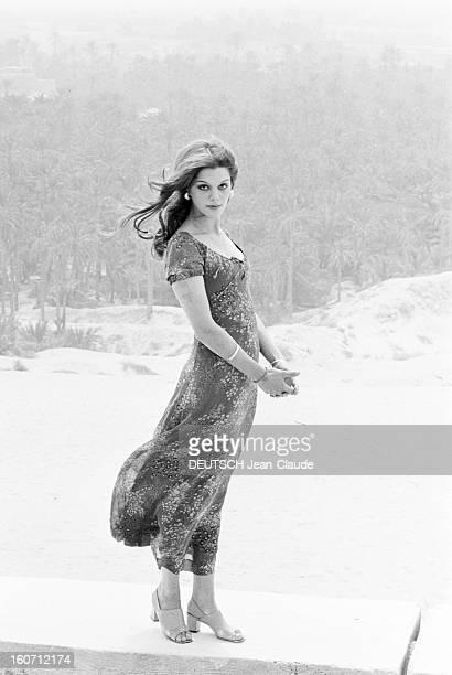 Tina Aumont Shows Spring 1971 Paris Fashion In Tunisia. En Tunisie, à Nefta, Tina AUMONT, debout sur un muret, dans un paysage aride, présentant pour...