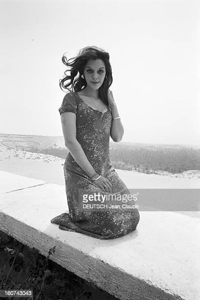 Tina Aumont Shows Spring 1971 Paris Fashion In Tunisia. En Tunisie, à Nefta, Tina AUMONT, agenouillée sur un muret, dans un paysage aride, présentant...