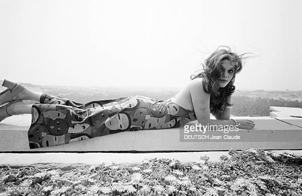 Tina Aumont Shows Spring 1971 Paris Fashion In Tunisia En Tunisie à Nefta Tina AUMONT allongée sur un muret dans un paysage aride présentant pour la...