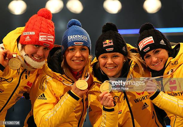 Tina Bachmann, Magdalena Neuner, Miriam Goessner and Andrea Henkel of Germany celebrate their gold medal for the Women's 4 x 6km Relay during the IBU...