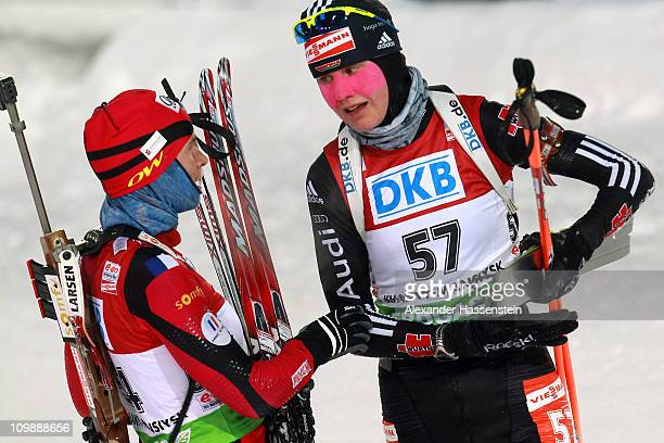 Tina Bachmann of Germany talks to Anais Bescond of France at the finish area after the women's 15km individual race during the IBU Biathlon World...