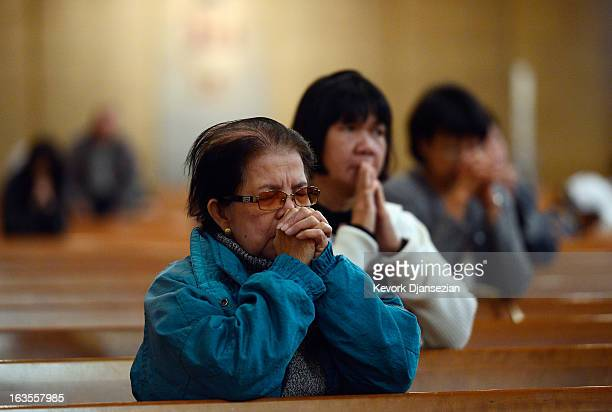 Tina Carreon prays during Votive Mass that concluded the twelve hour prayer vigil in advance of the election of a new Pope at the Cathedral of Our...