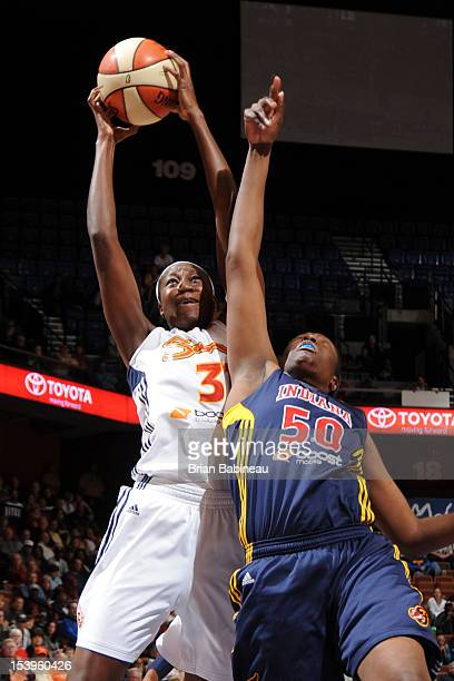 Tina Charles of the Connecticut Sun grabs a rebound against Jessica Davenport of the Indiana Fever during Game Three of the Eastern Conference Finals...
