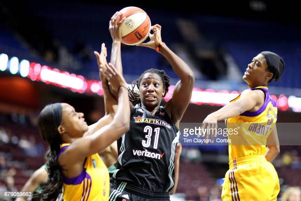 Tina Charles of the New York Liberty rebounds while challenged by Saicha GrantAllen of the Los Angeles Sparks and Chelsea Hopkins of the Los Angeles...