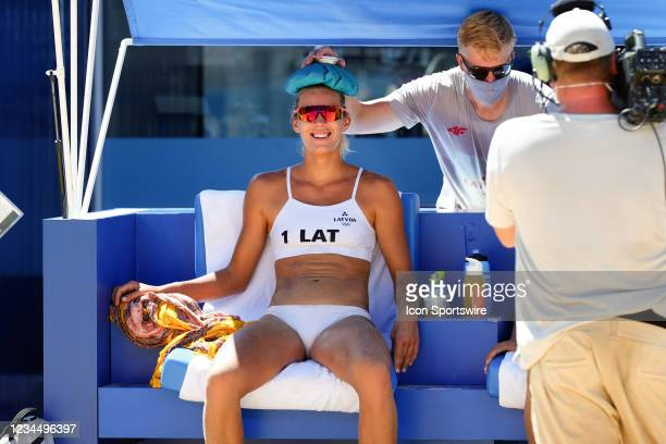 Tina Graudina of Team Latvia takes a break in the heat during the Women's Beach Volleyball Bronze Medal match between Latvia and Switzerland on Day...