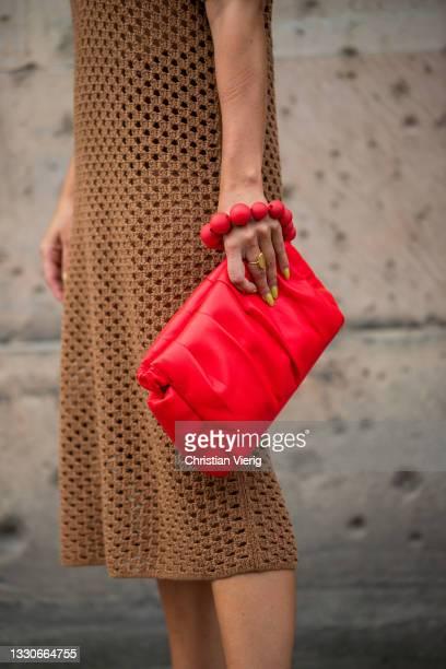 Tina Haase is seen wearing Chanel sunglasses, h&m crochet dress in brown, Essentiel Antwerp Bag in red, Zara heels on July 25, 2021 in Berlin,...