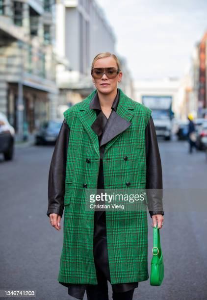 Tina Haase is seen wearing checkered Baum& Pferdgarten green vest sleeveless coat, NORR leather Blouson & skirt, Zara boots, H&M trend Sunglasses,...
