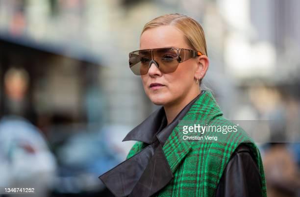 Tina Haase is seen wearing checkered Baum& Pferdgarten green vest sleeveless coat, NORR leather Blouson & skirt, Zara boots, H&M trend Sunglasses on...