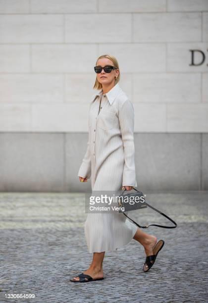 Tina Haase is seen wearing Nanushka dress in creme white, Jil Sander flats in black, Jacquemus bag, Chanel sunglasses on July 25, 2021 in Berlin,...