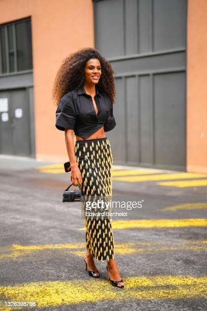 Tina Kunakey wears a black cropped shirt, a black high-waist long skirt with yellow attached sticks, a black mini leather Jacquemus bag, black high...