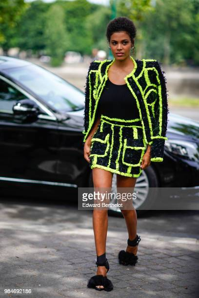 Tina Kunakey wears a jacket with yellow lines outside Balmain during Paris Fashion Week Menswear SpringSummer 2019 on June 24 2018 in Paris France