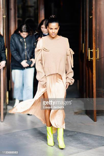 Tina Kunakey wears a wool pullover, a pleated silky skirt, yellow shoes, outside Stella McCartney, during Paris Fashion Week Womenswear Fall/Winter...