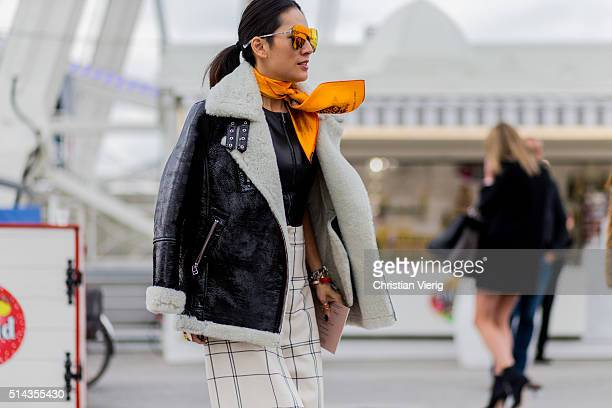 Tina Leung is wearing a black shearling fur leather jacket and an orange scarf outside Valentino during the Paris Fashion Week Womenswear Fall/Winter...