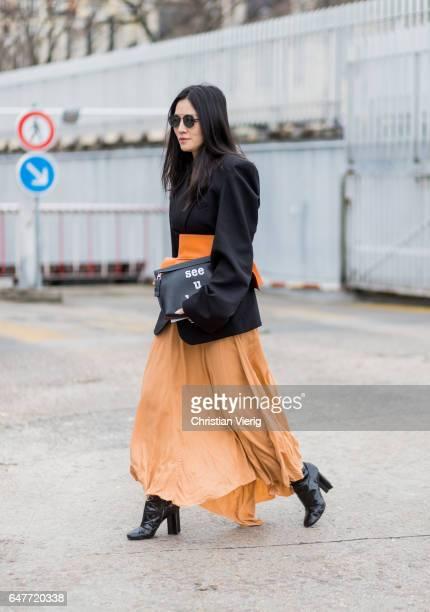 Tina Leung wearing black jacket orange shirt Loewe clutch outside Loewe on March 3 2017 in Paris France