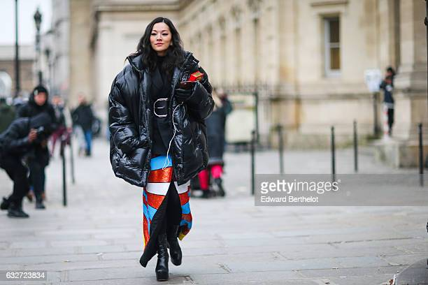 Tina Leung wears a black large puffer coat a black jacket a large belt and a colored skirt outside the Jean Paul Gaultier show during Paris Fashion...