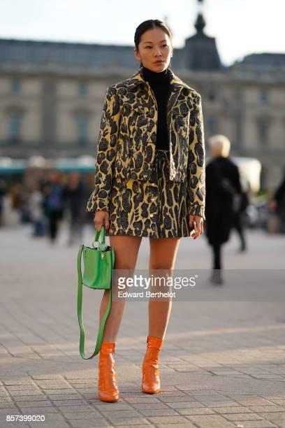 Tina Leung wears a black turtleneck top a leopard print jakcet a skirt orange boots a green bag outside Louis Vuitton during Paris Fashion Week...