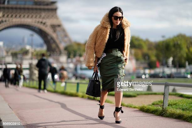 Tina Leung wears a fur coat a black top a green skirt outside Hermes during Paris Fashion Week Womenswear Spring/Summer 2018 on October 2 2017 in...