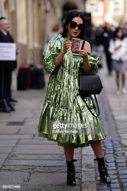 Tina Leung wears a green shiny ruffled dress a black leather bag sunglasses black shoes and uses a smartphone during London Fashion Week September...