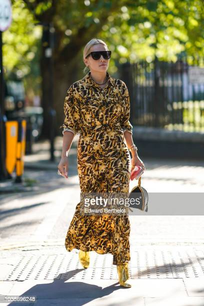 Tina Leung wears a leopard print dress yellow shoes a black bag during London Fashion Week September 2018 on September 16 2018 in London England