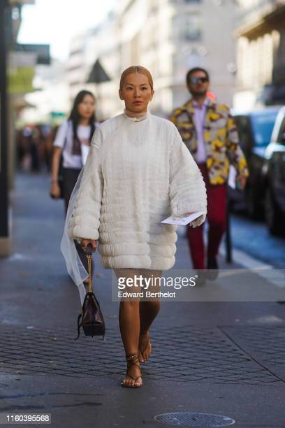 Tina Leung wears a white lace dress a Valentino bag heels shoes outside Valentino during Paris Fashion Week Haute Couture Fall/Winter 2019/2020 on...