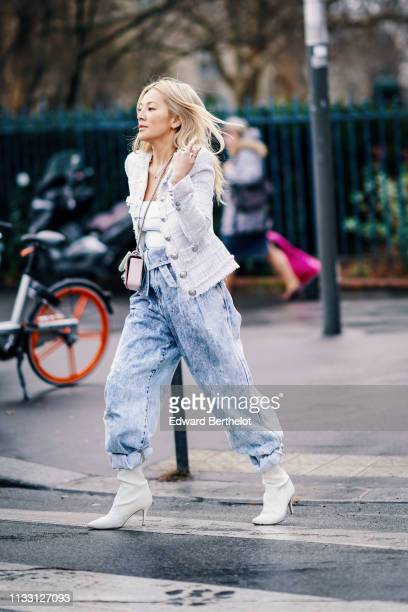 Tina Leung wears a white tweed jacket with buttons, blue jeans, white shoes with heels, a white top, outside Balmain, during Paris Fashion Week...