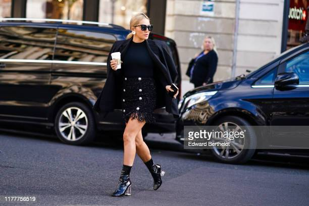 Tina Leung wears earrings, sunglasses, a black top, a black jacket, a black Lurex and tweed fringy mini dress with buttons,, shiny black patent...