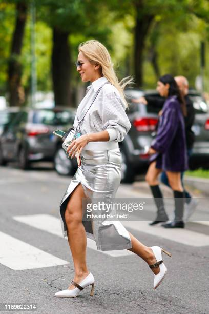 Tina Leung wears sunglasses, a white jacket, a white belt, a shiny silver-tone front-split skirt, white pointy heeled pumps with a brown strap,...