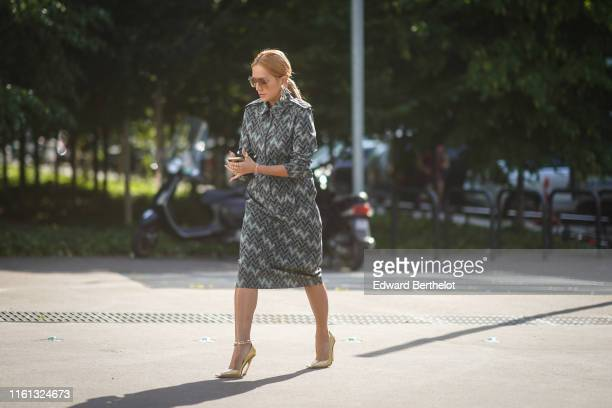 Tina Leung wears sunglasses earrings rings a bracelet a grey dress with geometric designs an anklet shiny golden color heeled pumps outside Acne...