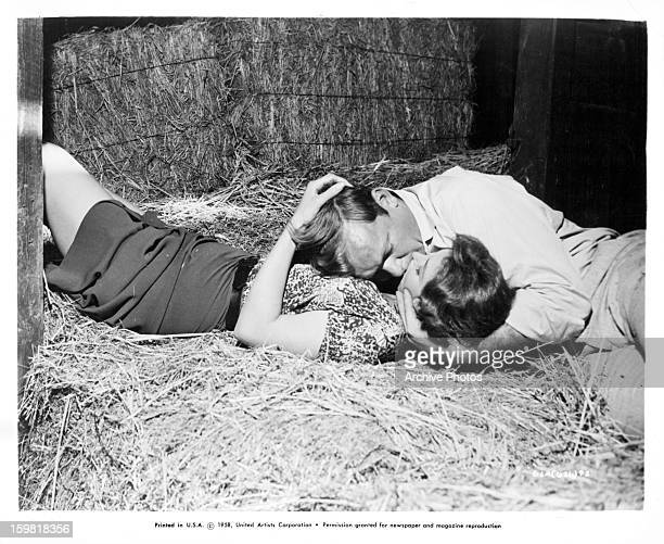 Tina Louise and Aldo Ray kissing in the hay in a scene from the film 'God's Little Acre' 1958