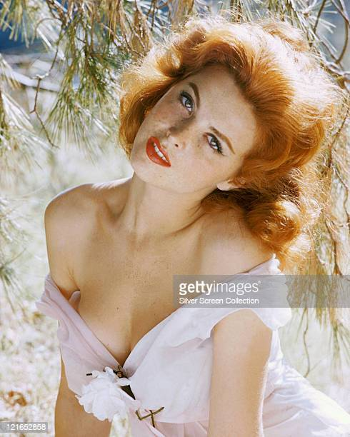 Tina Louise US actress and singer wearing a white tope which has fallen down from her shoulders with a white flower on the front circa 1960