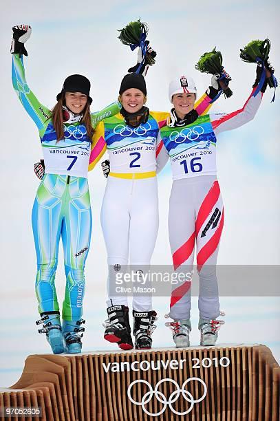 Tina Maze of Slovenia celebrates winning the silver medal Viktoria Rebensburg of Germany gold and Elisabeth Goergl of Austria bronze during the...